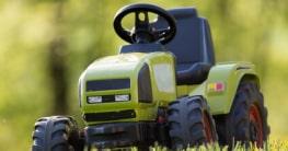 Kindertraktor mit Motor steht auf einer Wiese